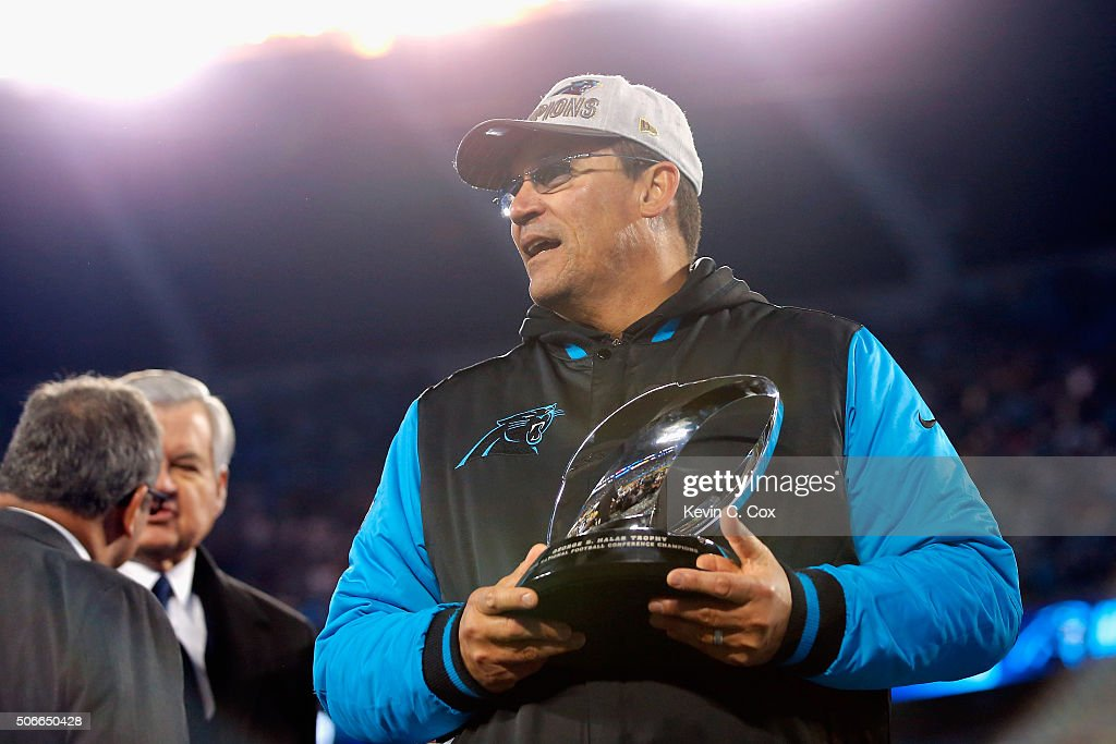 Head coach Ron Rivera of the Carolina Panthers celebrates with the George Halas Trophy after defeating the Arizona Cardinals with a score of 49 to 15...