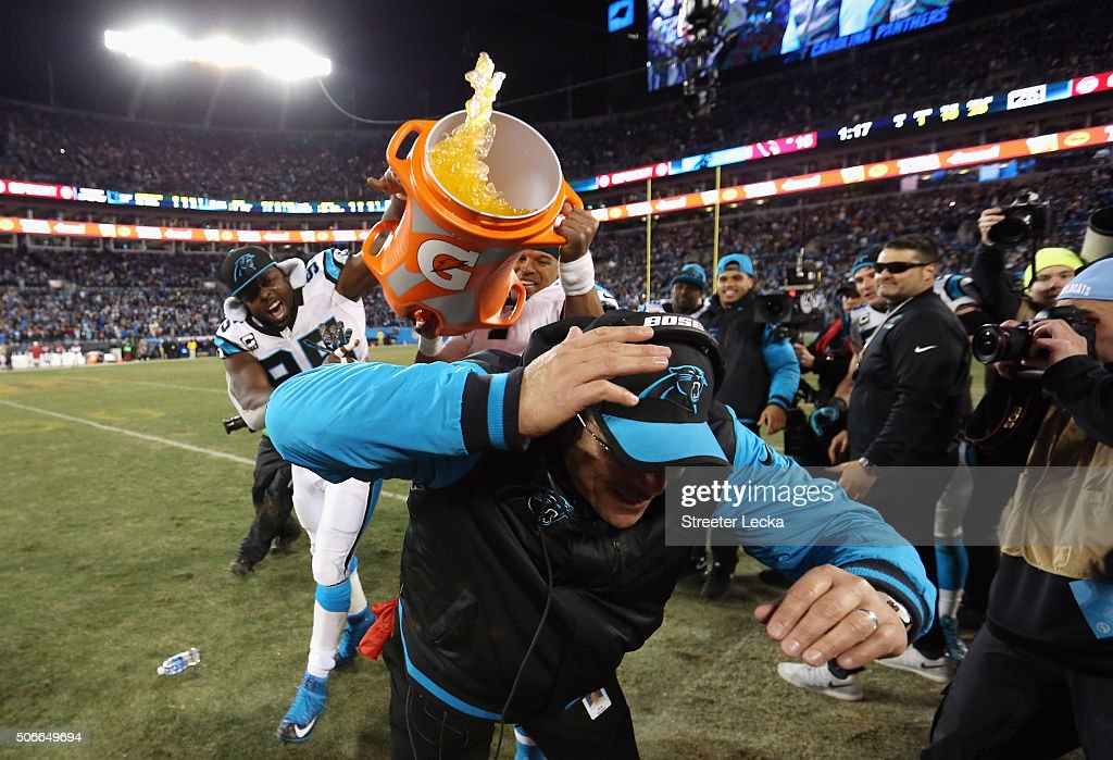 Head coach Ron Rivera of the Carolina Panthers is doused with Gatorade by Charles Johnson and Cam Newton after the Carolina Panthers defeat the...