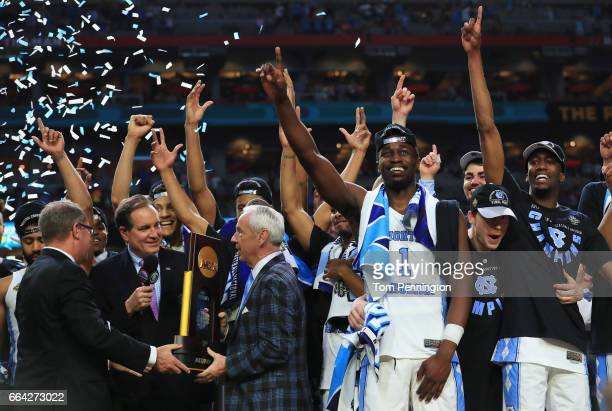 Head coach Roy Williams of the North Carolina Tar Heels receives the Championship trophy after defeating the Gonzaga Bulldogs during the 2017 NCAA...