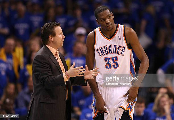 Head coach Scott Brooks of the Oklahoma City Thunder talks with Kevin Durant in the third quarter while taking on the Dallas Mavericks in Game Four...