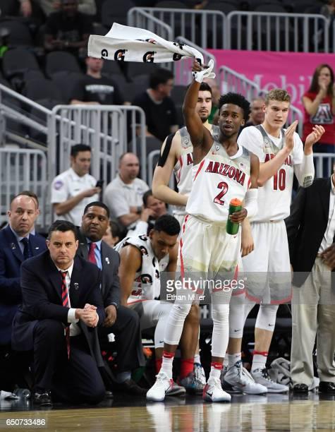 Head coach Sean Miller of the Arizona Wildcats looks on as Kobi Simmons and Lauri Markkanen of the Arizona Wildcats celebrate a teammate's basket...