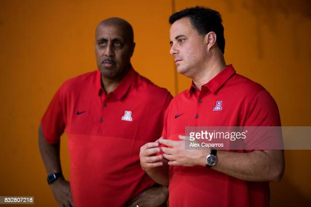 Head Coach Sean Miller of the Arizona Wildcats speaks to Associate Head Coach Lorenzo Romar during the Arizona In Espana Foreign Tour game between...