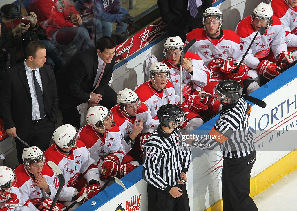 Head coach Sheldon Keefe of the Sault Ste. Marie Greyhounds gets an explanation on a play from referee Scott Oakman #23 in an OHL game against the London Knights on February 22, 2013 at the Budweiser Gardens in London, Ontario, Canada. The Knights defeated the Greyhounds 4-3 in overtime.