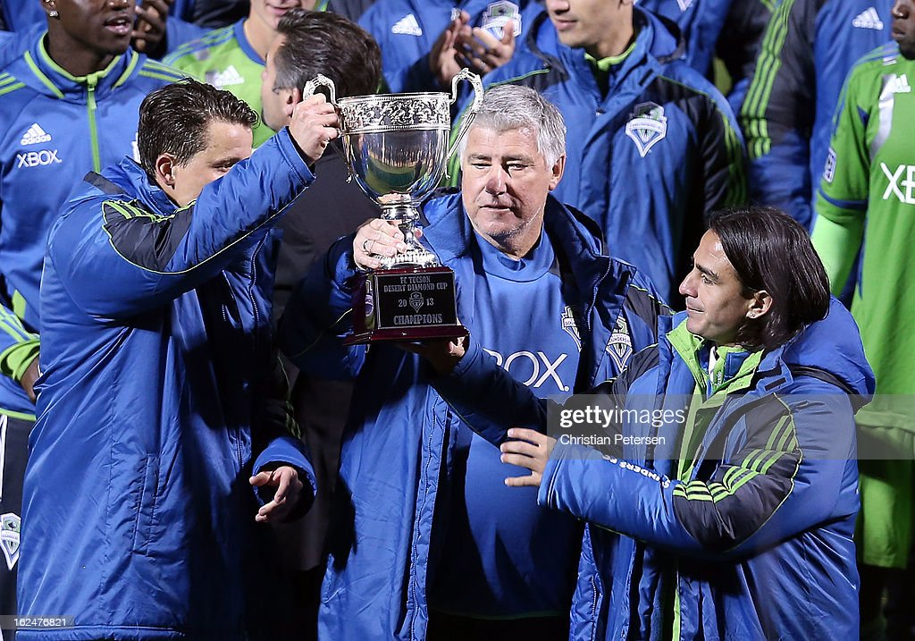 Head coach Sigi Schmid (C) and Mauro Rosales (R) of the Seattle Sounders hold up the FC Tucson Desert Diamond Cup after defeating Real Salt Lake 1-0 in the Championship match at Kino Sports Complex on February 23, 2013 in Tucson, Arizona.