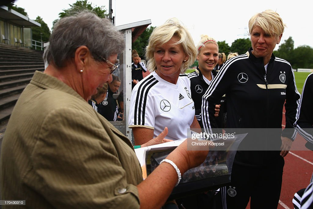 Head coach <a gi-track='captionPersonalityLinkClicked' href=/galleries/search?phrase=Silvia+Neid&family=editorial&specificpeople=641230 ng-click='$event.stopPropagation()'>Silvia Neid</a> (2nd L) and managewr <a gi-track='captionPersonalityLinkClicked' href=/galleries/search?phrase=Doris+Fitschen&family=editorial&specificpeople=2382890 ng-click='$event.stopPropagation()'>Doris Fitschen</a> (R) speak to a fan during the training session of Women's Team Germany at training ground Ueberruhr on June 13, 2013 in Essen, Germany.