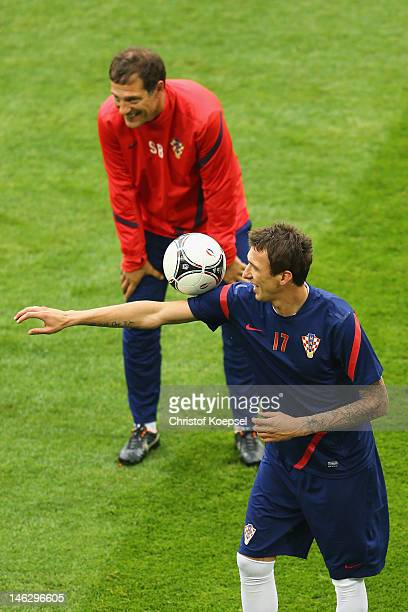 Head coach Slaven Bilic of Croatia watches Mario Mandzukic juggling with the ball during a UEFA EURO 2012 training session at the Municipal Stadium...