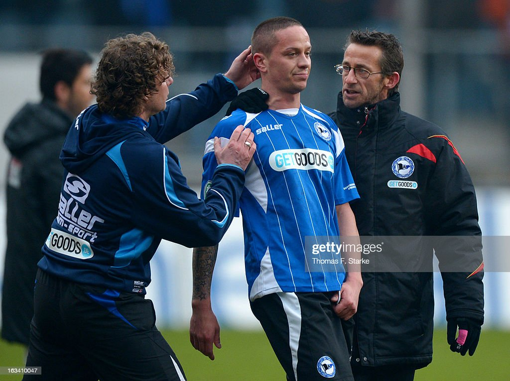 Head coach Stefan Kraemer (L) and assistant coach Nils Haacke (R) comfort Bielefeld player Christian Mueller who missed a penalty after the Third League match between Arminia Bielefeld and Preussen Muenster at Schueco Arena on March 9, 2013 in Bielefeld, Germany.