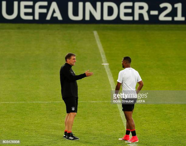 Head coach Stefan Kuntz of Germany talks with team mate Serge Gnabry of Germany during the MD1 training session of the U21 national team of Germany...