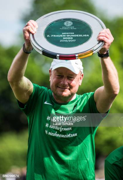 Head Coach Steffen Rau holds the trophy after winning the championship of the Second Bundesliga Nord after the match between Werder Bremen and VfL...