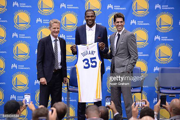 Head coach Steve Kerr of the Golden State Warriors Kevin Durant and General Manager Bob Myers display the jersey of Kevin Durant Golden State...