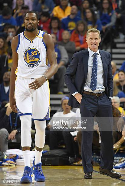 Head coach Steve Kerr of the Golden State Warriors looks on smiling as Kevin Durant walks back down court during a break in the action against the...