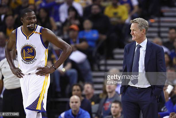 Head coach Steve Kerr of the Golden State Warriors talks to Kevin Durant during their preseason game against the Los Angeles Clippers at ORACLE Arena...