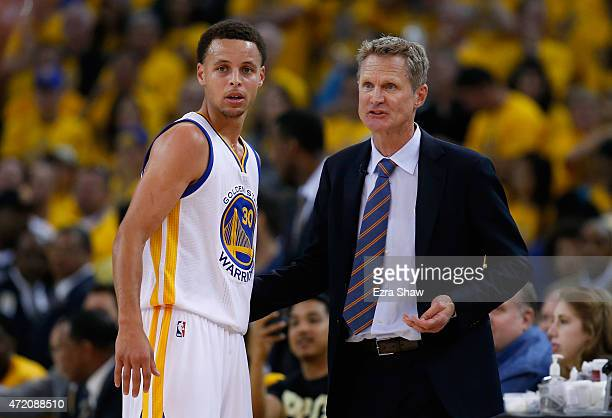 Head coach Steve Kerr of the Golden State Warriors talks to Stephen Curry during their game against the Memphis Grizzlies during Game One of the...