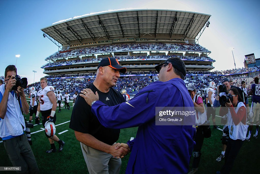 Head coach Steve Sarkisian of the Washington Huskies (R) is congratulated by head coach Mike Kramer of the Idaho State Bengals after the Huskies defeated the Bengals 56-0 on September 21, 2013 at Husky Stadium in Seattle, Washington.