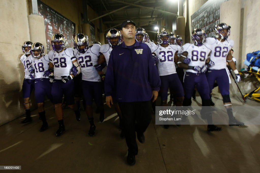 Head coach Steve Sarkisian of the Washington Huskies leads the team onto the field before a game against the Stanford Cardinal on October 5, 2013 at Stanford Stadium in Stanford, California.
