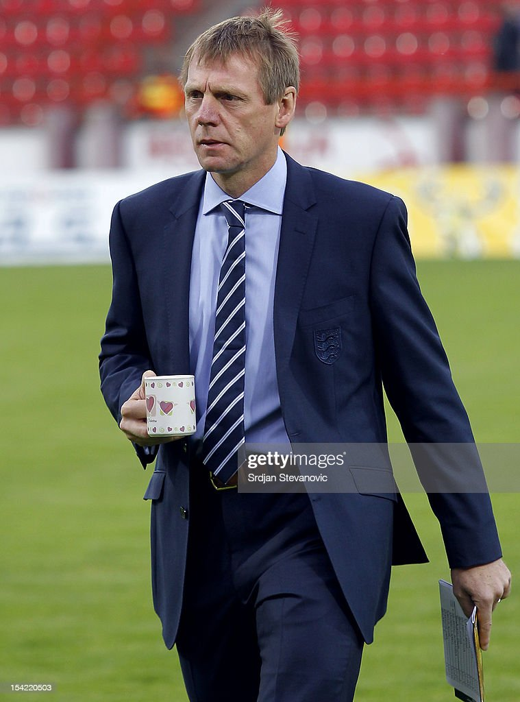 Head coach Stuart Pearce walks across the pitch holding a mug prior to the Under 21 European Championship Play Off second leg match between Serbia U21 and England U21 at Stadium Mladost on October 16, 2012 in Krusevac, Serbia.