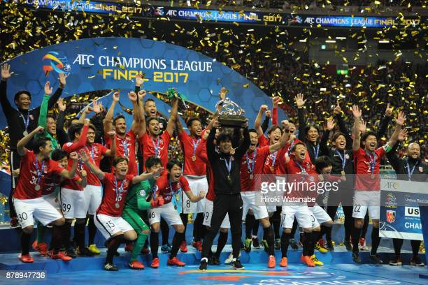 Head coach Takafumi Hori of Urawa Red Diamonds lifts the AFC Champions League trophy at the award ceremony during the AFC Champions League Final...