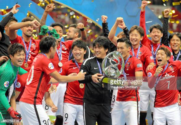 Head coach Takafumi Hori of Urawa Red Diamonds lifts the trophy at the award ceremony after the AFC Champions League Final second leg match between...
