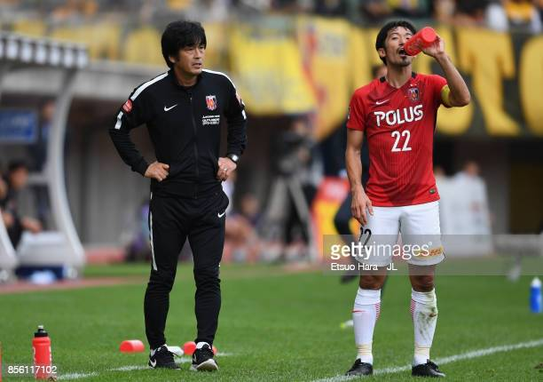 Head coach Takafumi Hori of Urawa Red Diamonds talks to Yuki Abe during the JLeague J1 match between Vegalta Sendai and Urawa Red Diamonds at Yurtec...