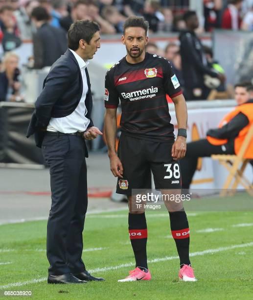 Head coach Tayfun Korkut of Leverkusen speak with t Karim Bellarabi during the Bundesliga match between Bayer 04 Leverkusen and VfL Wolfsburg at...