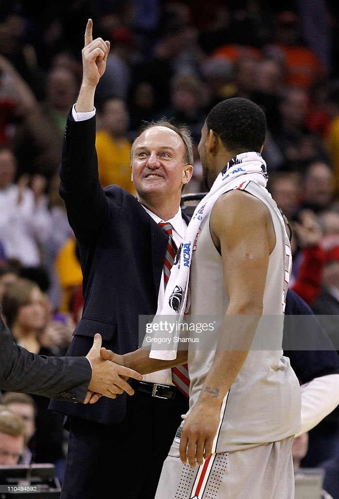 Head coach <a gi-track='captionPersonalityLinkClicked' href=/galleries/search?phrase=Thad+Matta&family=editorial&specificpeople=799910 ng-click='$event.stopPropagation()'>Thad Matta</a> of the Ohio State Buckeyes stands on the court with David Lighty #23 after defeating the George Mason Patriots during the third of the 2011 NCAA men's basketball tournament at Quicken Loans Arena on March 20, 2011 in Cleveland, Ohio.