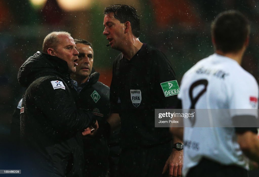 Head coach thomas Schaaf of Bremen talks to referee Manuel Graefe during the Bundesliga match between SV Werder Bremen and 1. FSV Mainz 05 at Weser Stadium on November 4, 2012 in Bremen, Germany.