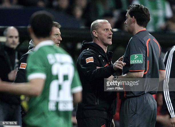 Head coach Thomas Schaaf of Bremen talks to Referee Manuel Graefe during the DFB Cup Semi Final match between SV Werder Bremen and FC Augsburg at...