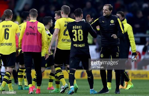 Head coach Thomas Tuchel of Dormtund celebrates with goalkeeper Roman Buerki of Dortmund after winning the Bundesliga match between Borussia...