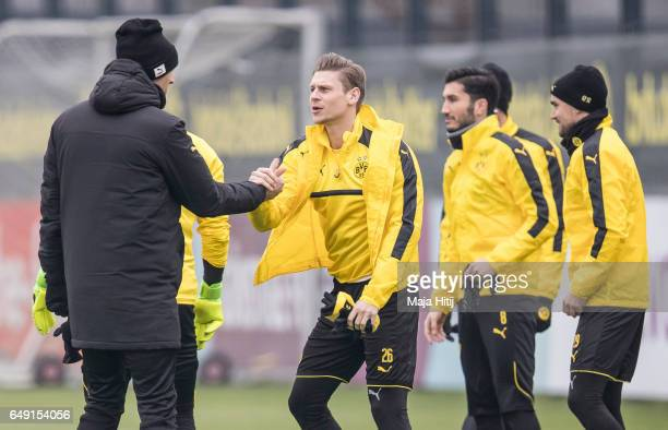 Head coach Thomas Tuchel of Dortmund and Lukasz Piszczek talk prior the training of Borussia Dortmund ahead of the UEFA Champions League Round of 16...