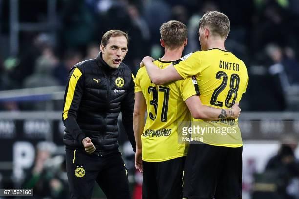 Head coach Thomas Tuchel of Dortmund Erik Durm and Matthias Ginter celebrate after the Bundesliga match between Borussia Moenchengladbach and...