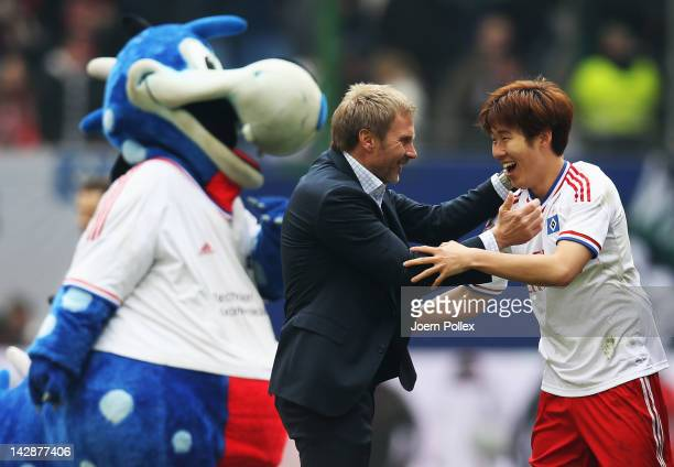 Head coach Thorsten Fink and Heung Min Son of Hamburg celebrate after winning the Bundesliga match between Hamburger SV and Hannover 96 at Imtech...
