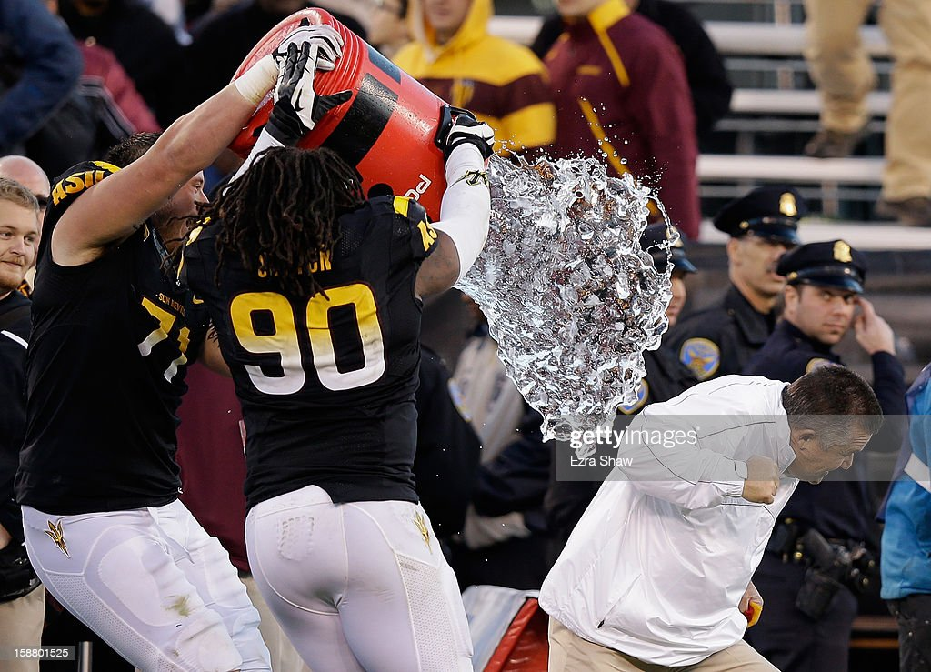 Head coach Todd Graham of the Arizona State Sun Devils is dumped with water by Will Sutton #90 of the Arizona State Sun Devils after they beat the Navy Midshipmen in the Kraft Fight Hunger Bowl at AT&T Park on December 29, 2012 in San Francisco, California.
