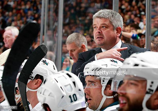 Head coach Todd McLellan of the San Jose Sharks looks on from the bench during their NHL game against the Vancouver Canucks at Rogers Arena on...