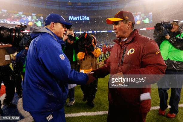 head coach Tom Coughlin of the New York Giants and head coach Mike Shanahan of the Washington Redskins shake hands following the game at MetLife...