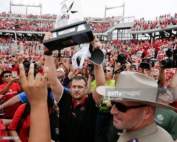 Head coach Tom Hermann of the Houston Cougars lifts up the Western Division Championship trophy after beating Navy 5231 at TEDECU Stadium on November...