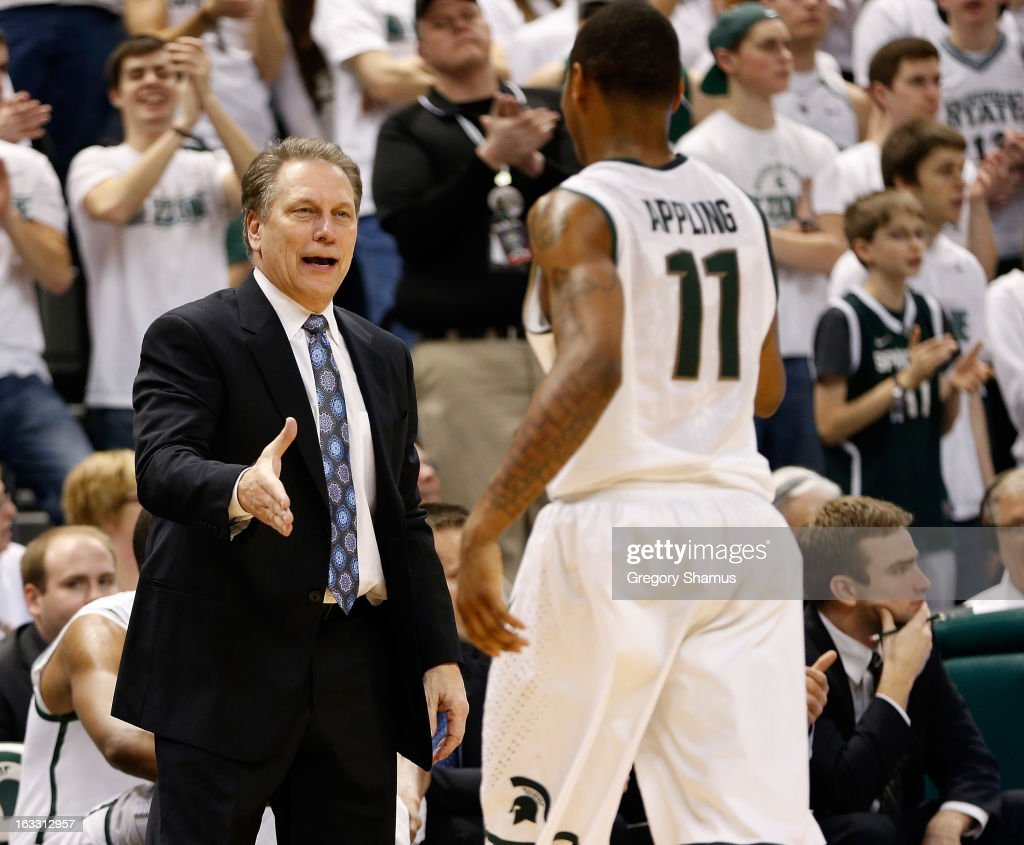 Head coach <a gi-track='captionPersonalityLinkClicked' href=/galleries/search?phrase=Tom+Izzo&family=editorial&specificpeople=238861 ng-click='$event.stopPropagation()'>Tom Izzo</a> of the Michigan State Spartans congratulates Keith Appling #11 as he leaves the floor in the second half while playing the Wisconsin Badgers at the Jack T. Breslin Student Events Center on March 7, 2013 in East Lansing, Michigan. Michigan State won the game 58-43.