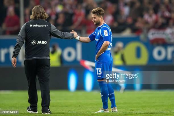 Head Coach Torsten Frings and Markus Steinhoefer of Darmstadt shake hands after loosing the Second Bundesliga match between Fortuna Duesseldorf and...
