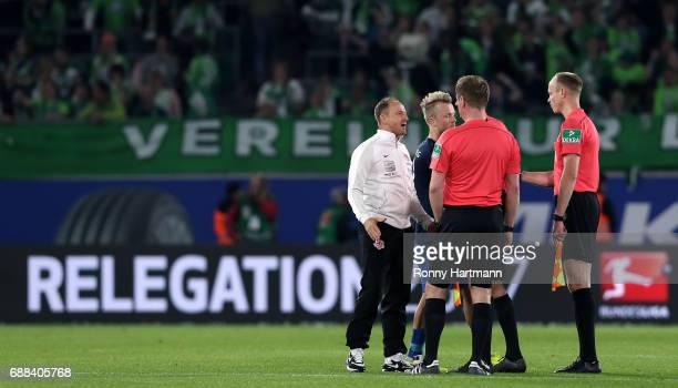 Head coach Torsten Lieberknecht of Braunschweig discusses with the referee team after the Bundesliga Playoff first leg match between VfL Wolfsburg...