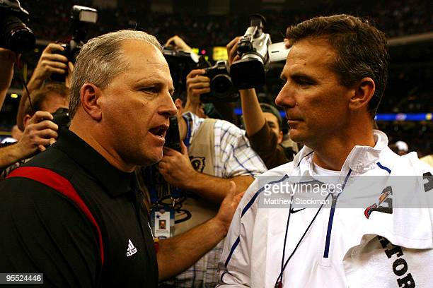 Head coach Urban Meyer of the Florida Gators talks with Interim head coach Jeff Quinn of the Cincinnati Bearcats after the Gators defeated the...