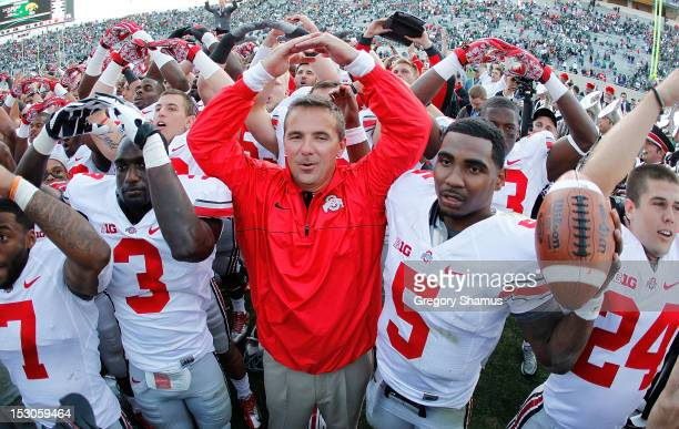 Head coach Urban Meyer of the Ohio State Buckeyes celebrates with his players after beating the Michigan State Spartans 1716 at Spartan Stadium on...