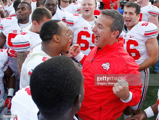Head coach Urban Meyer of the Ohio State Buckeyes celebrates with Etienne Sabino after beating the Michigan State Spartans 1716 at Spartan Stadium on...