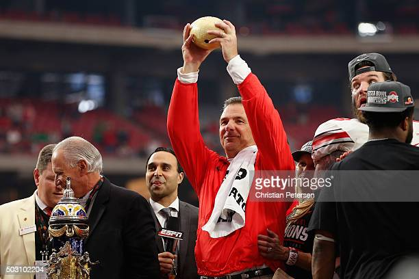 Head coach Urban Meyer of the Ohio State Buckeyes holds up the BattleFrog Fiesta Bowl trophy after defeating the Fighting Irish 4428 at University of...