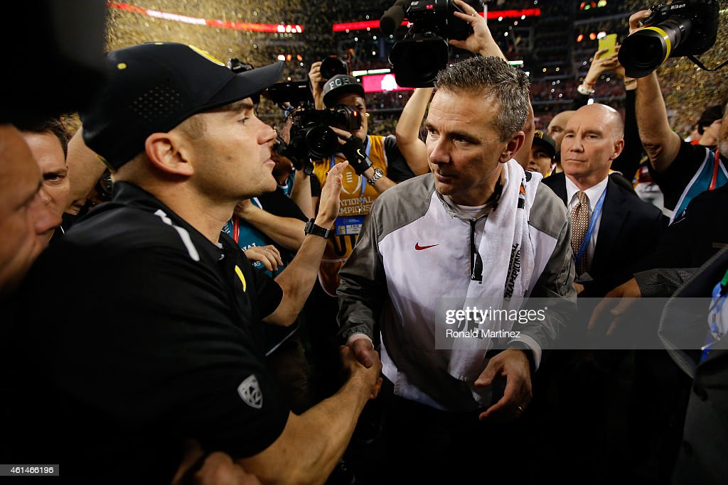 Head Coach Urban Meyer (R) of the Ohio State Buckeyes shakes hands with Head coach Mark Helfrich (L) of the Oregon Ducks after the College Football Playoff National Championship Game at AT&T Stadium on January 12, 2015 in Arlington, Texas. The Ohio State Buckeyes defeated the Oregon Ducks 42 to 20.