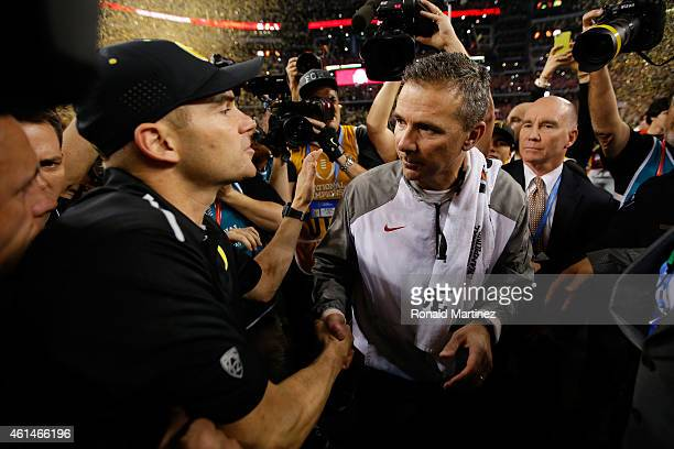 Head Coach Urban Meyer of the Ohio State Buckeyes shakes hands with Head coach Mark Helfrich of the Oregon Ducks after the College Football Playoff...