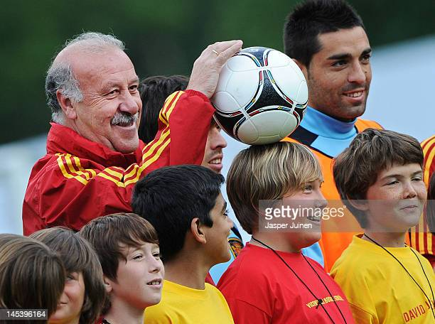 Head coach Vicente del Bosque of Spain balances a football on the head of a boy prior to the start of a training session on May 28 2012 in Schruns...