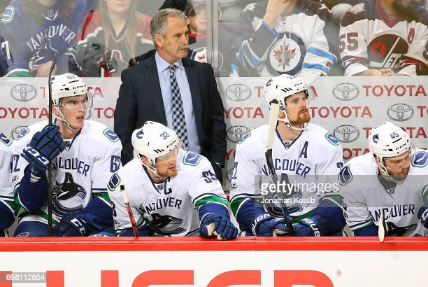 Head Coach Willie Desjardins Joseph LaBate Henrik Sedin Daniel Sedin and Michael Chaput of the Vancouver Canucks look on from the bench during third...