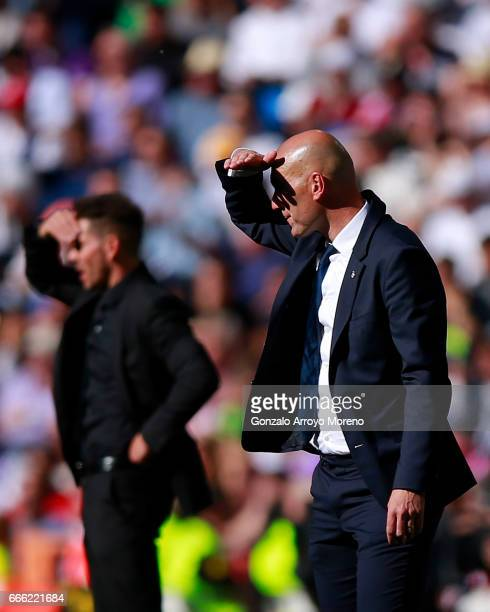 Head coach Zinedine Zidane of Real Madrid CF and head coach Diego Pablo Simeone of Atletico de Madrid cover their faces from the sun during the La...