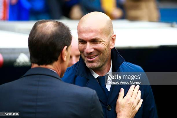 Head coach Zinedine Zidane of Real Madrid CF clashes hands with head coach Salvador alias Voro Gonzalez of Valencia CF during the La Liga match...