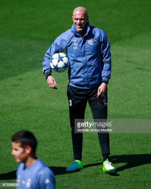 Head coach Zinedine Zidane of Real Madrid CF looks at his player James Rodriguez as he holds the ball druing a training session ahead of the UEFA...