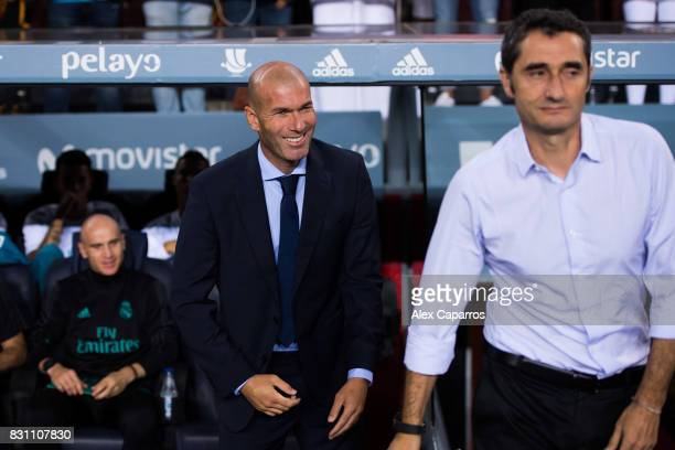 Head coach Zinedine Zidane of Real Madrid CF smiles next to Head coach Ernesto Valverde of FC Barcelona during the Supercopa de Espana Supercopa...